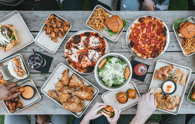 People sharing food and drinks on table - pizza, chicken wings, burgers, salad