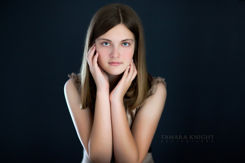 A beautiful girl framing her face with hands, a bot sitting. Siblings done by Orlando photographer