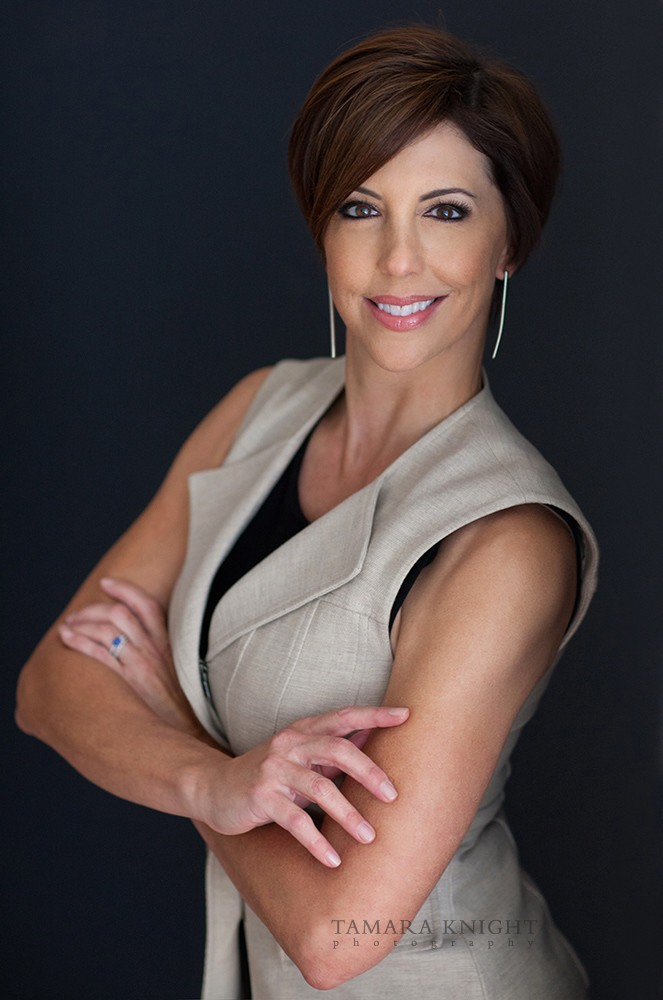 White woman with short brown hair, wearing vest, hands across chest