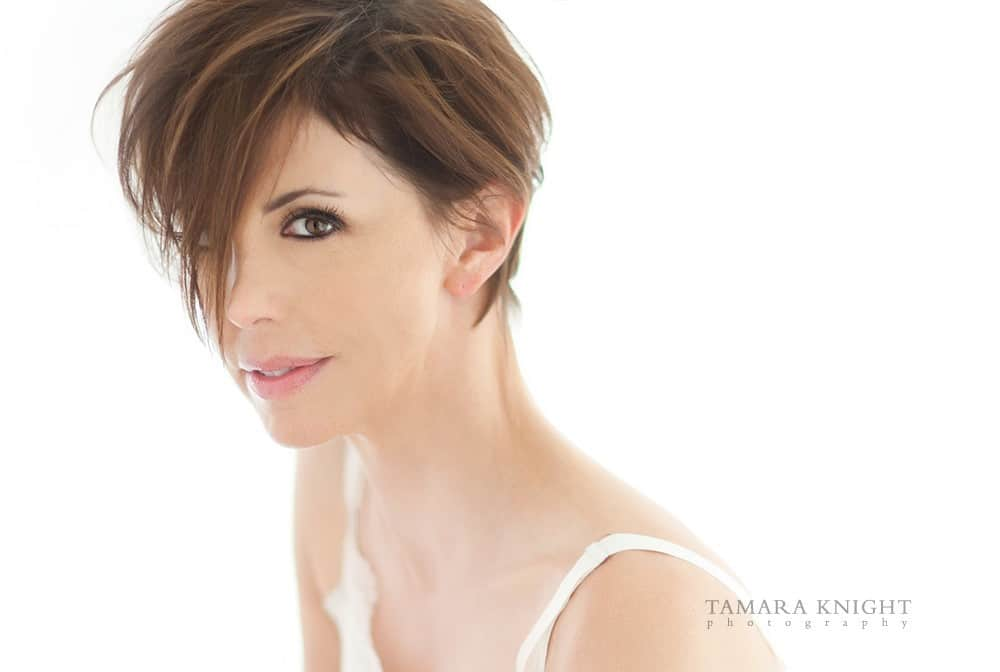 White woman with short brown hair in white camisole