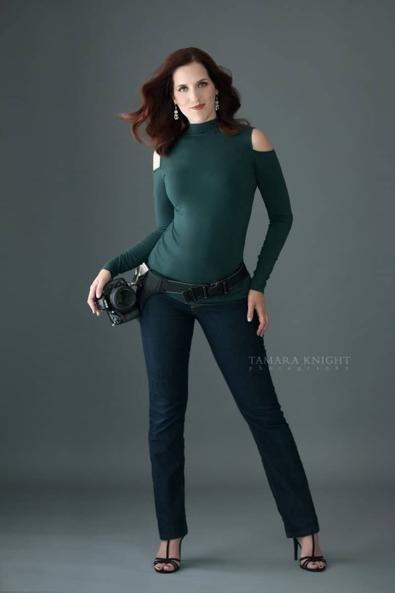 Portrait of woman wearing green top, jeans with camera on tool belt by Orlando Photographer