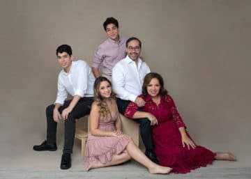 family with mom, dad, two sons and one daughter sitting for formal portrait
