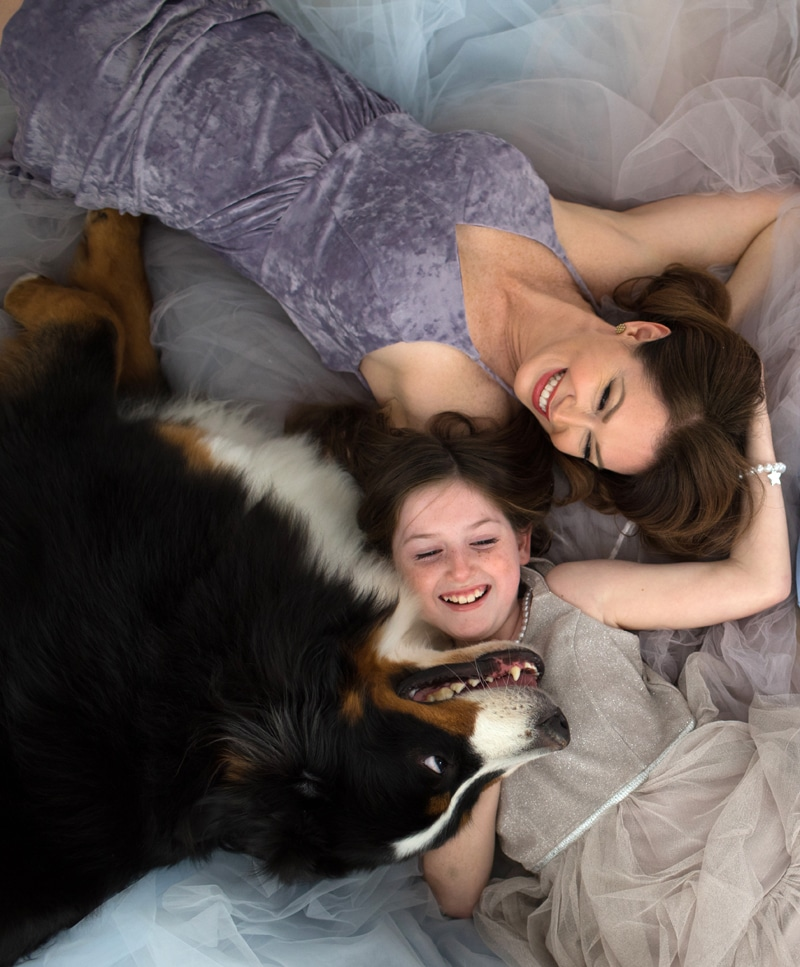 mother-daughter-and-dog-lying-on-floor-smiling