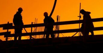 Construction Workers in Setting Sun