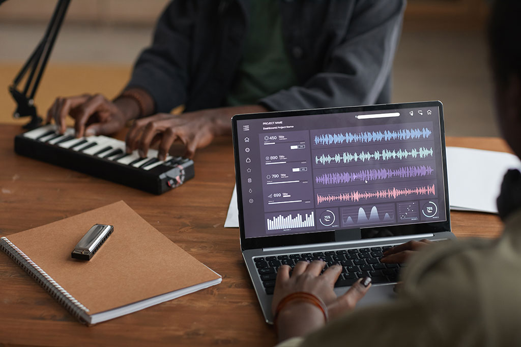 Close up of unrecognizable African-American musician using laptop with sound editing software
