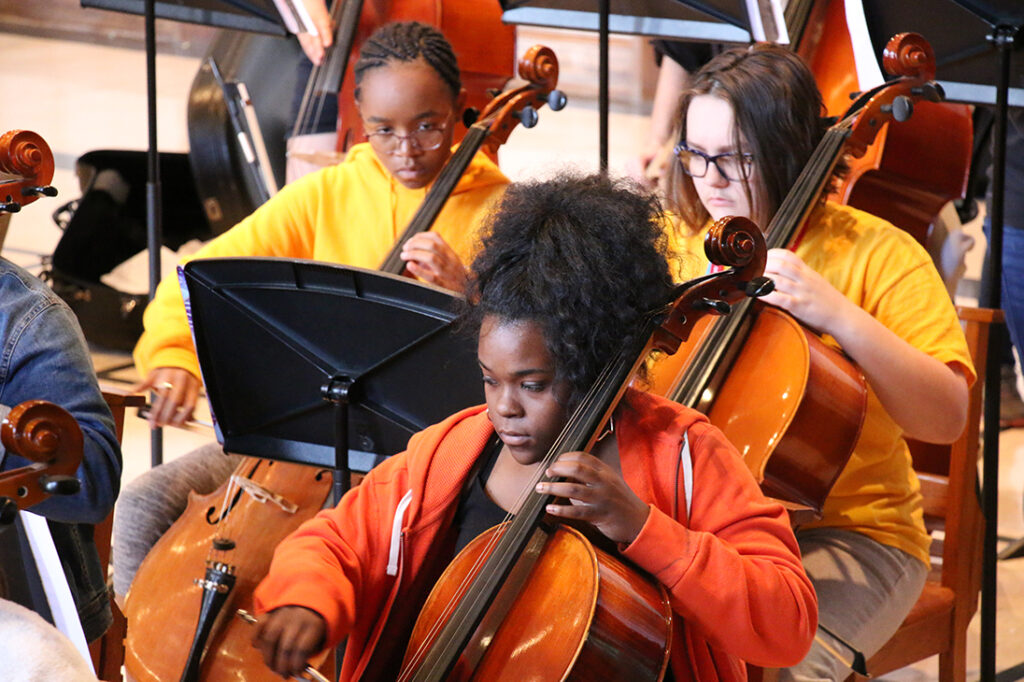 Young students playing bass instruments