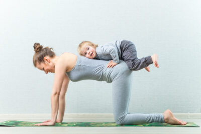 mom doing yoga exercises at home with child