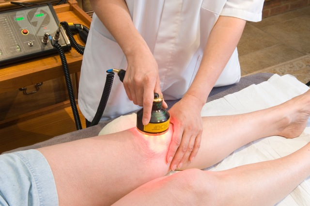 A doctor performing deep tissue laser therapy on a patient with knee pain