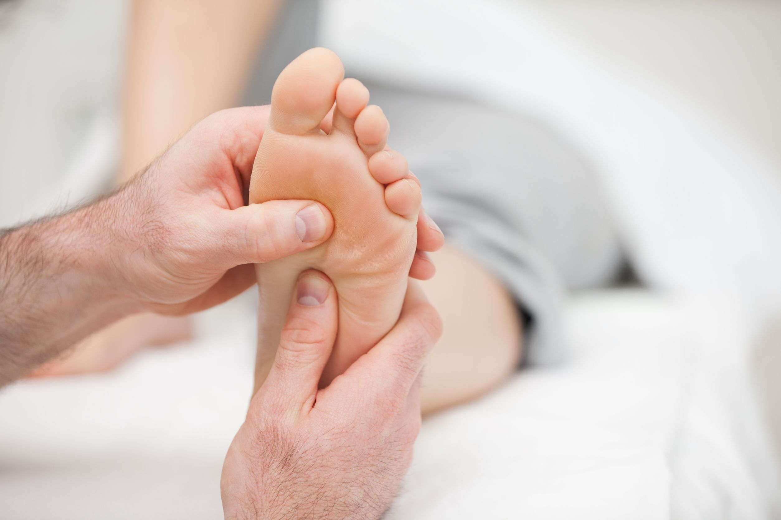 A doctor examining a woman with foot and ankle pain