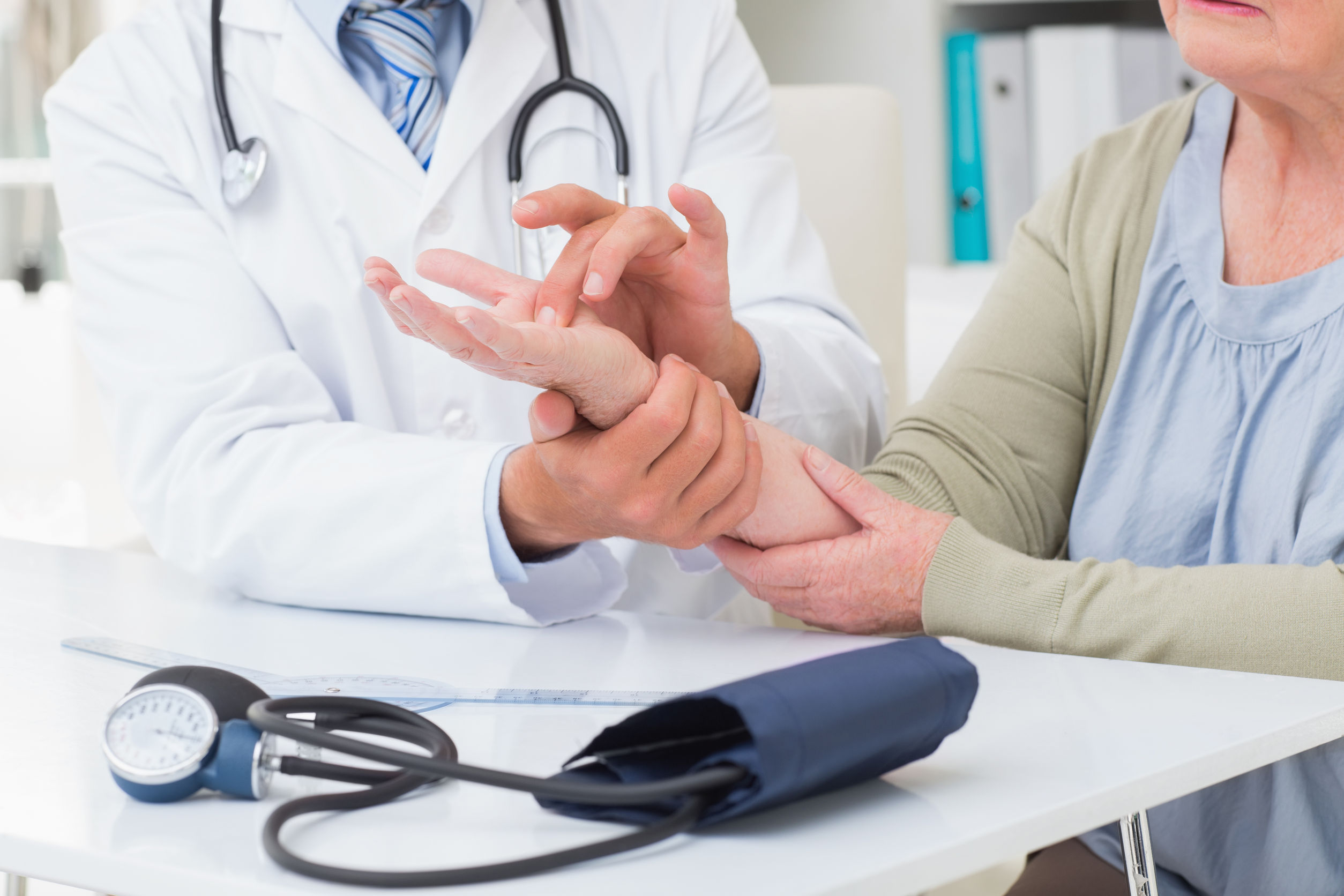 A doctor examining a patient's hand and wrist pain