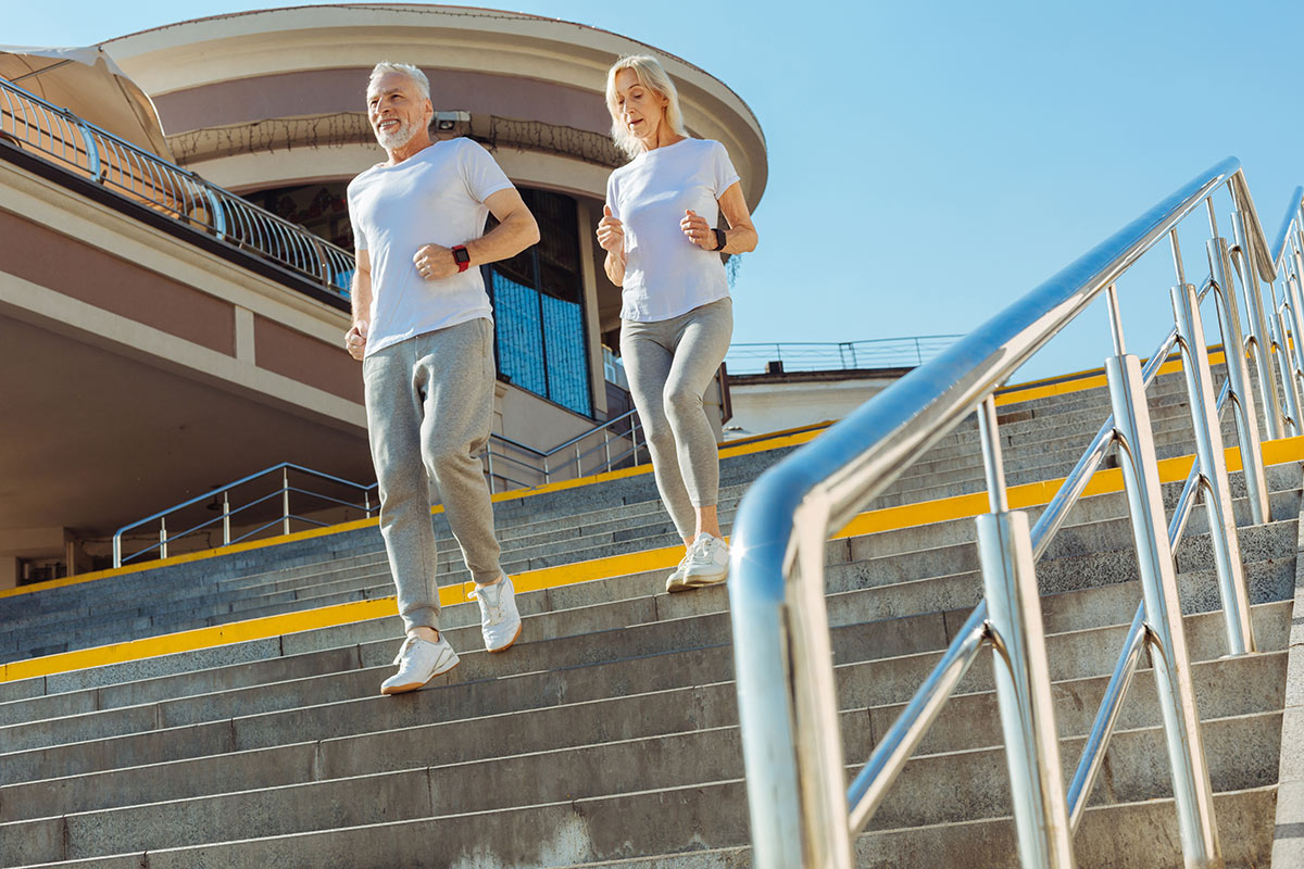 A man and woman jogging down steps