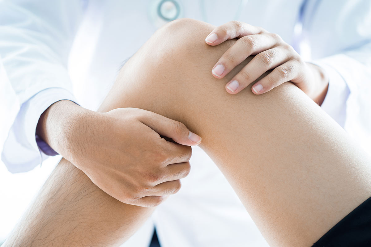A doctor performing physical therapy on a patient's knee