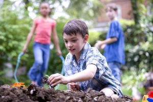 in-the-foreground-a-boy-in-the-shirt-is-playing-in-the-yard-725x483