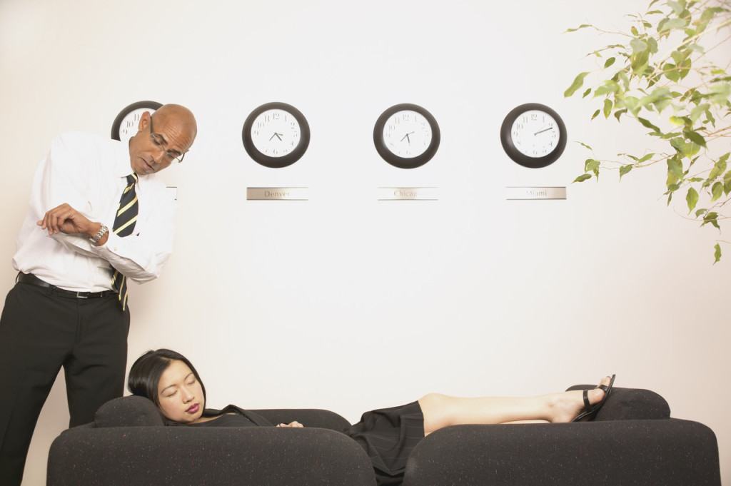 Young businessman standing over a young businesswoman sleeping on a couch