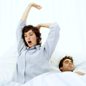 Woman Stretching in Bed with a Man Sleeping Beside Her