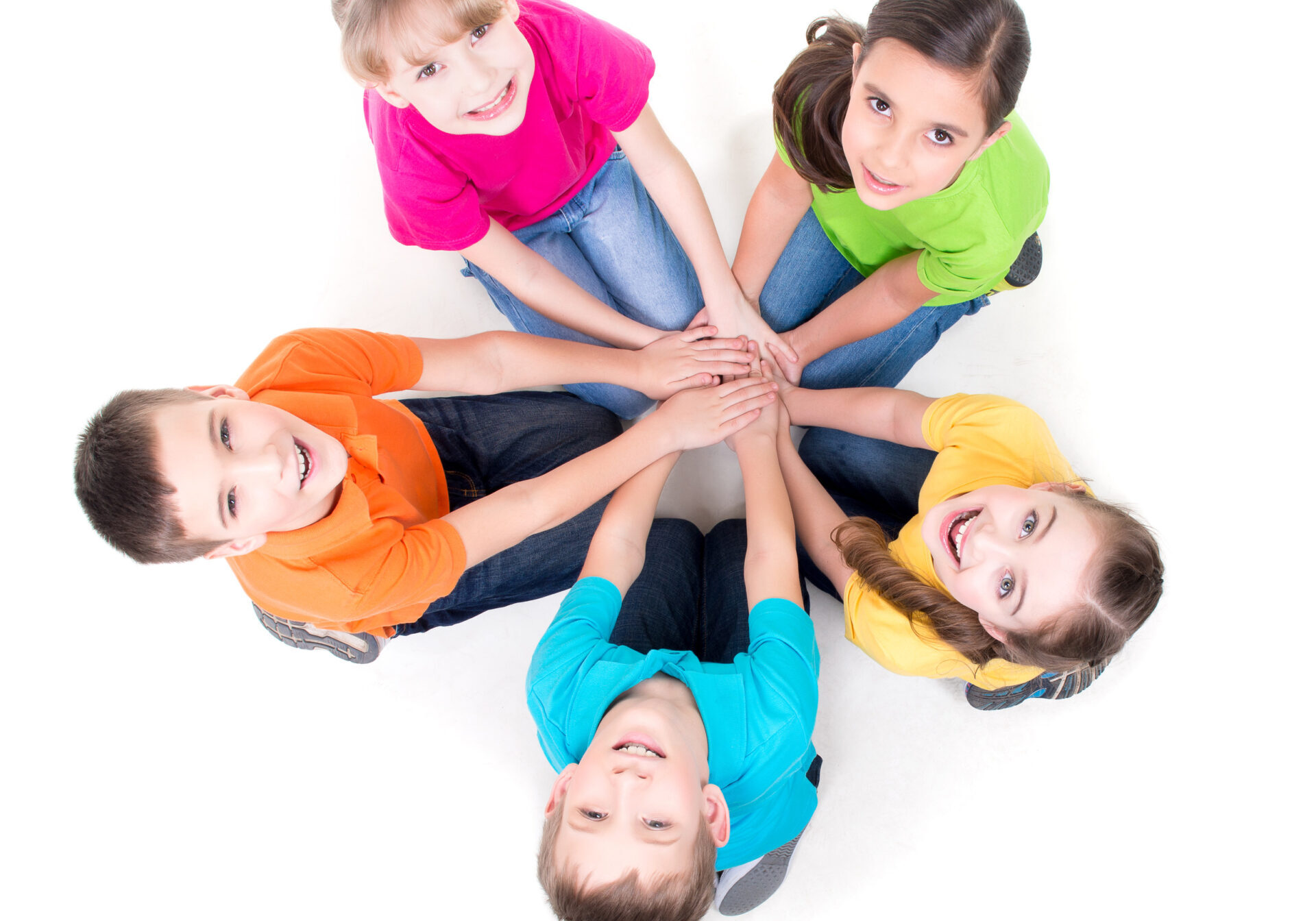 Group of happy children sitting on the floor in a circle holding hands and looking up - isolated on white.