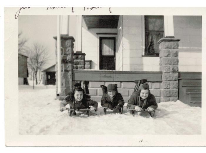 The Hartsell kids bundled up for  a sledding adventure, with their Mother (never called Mom), Edna looking through the window.