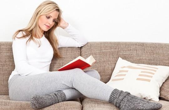 junge frau beim lesen auf dem sofa