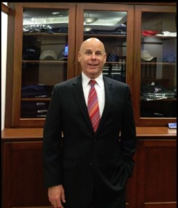 Jack Mizrahi standing in a suit with one hand in his pocket.
