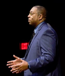 Photo of Dr. Wells presenting a talk. His hands are open and a microphone is visible by his left ear.