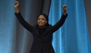 Ramona Smith with her arms raised on a stage.