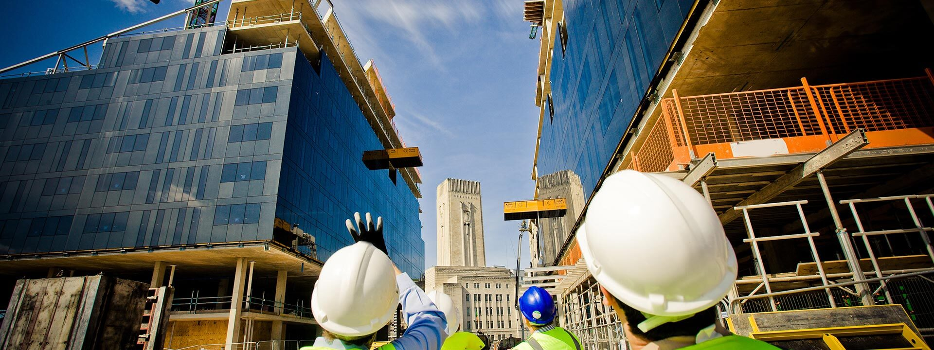 Construction workers looking up at a building site above
