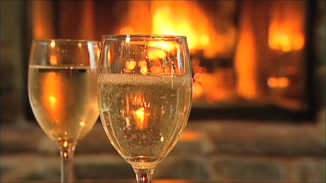 Romantic photo of 2 glasses of wine in front of the fire at Pearson's Pond Luxury Inn and Adventure Spa.
