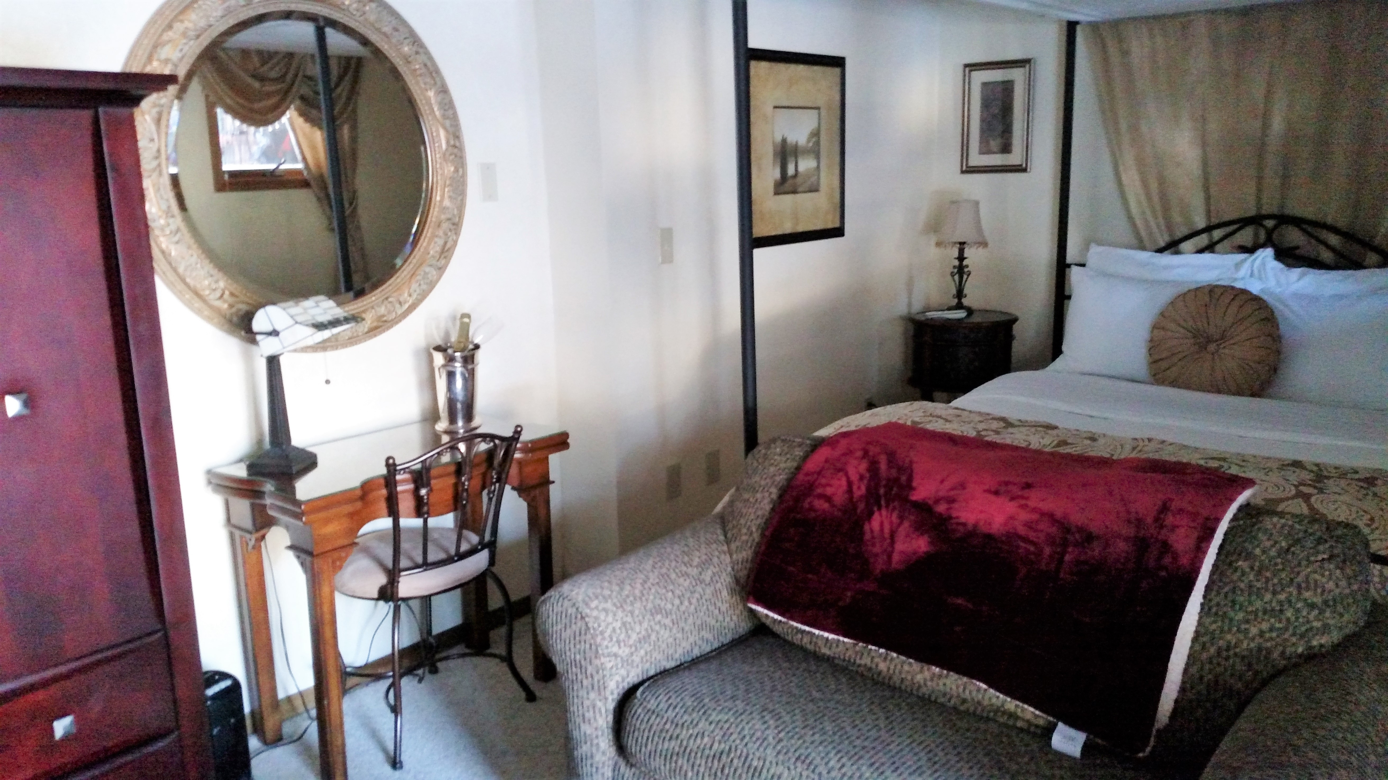 Photo of desk, bed and loveseat in Fireside deluxe studio at Pearson's Pond Luxury Inn and Adventure Spa.
