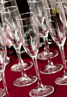 Close-up photo of our etched glass Pearson's Pond signature champagne flutes.