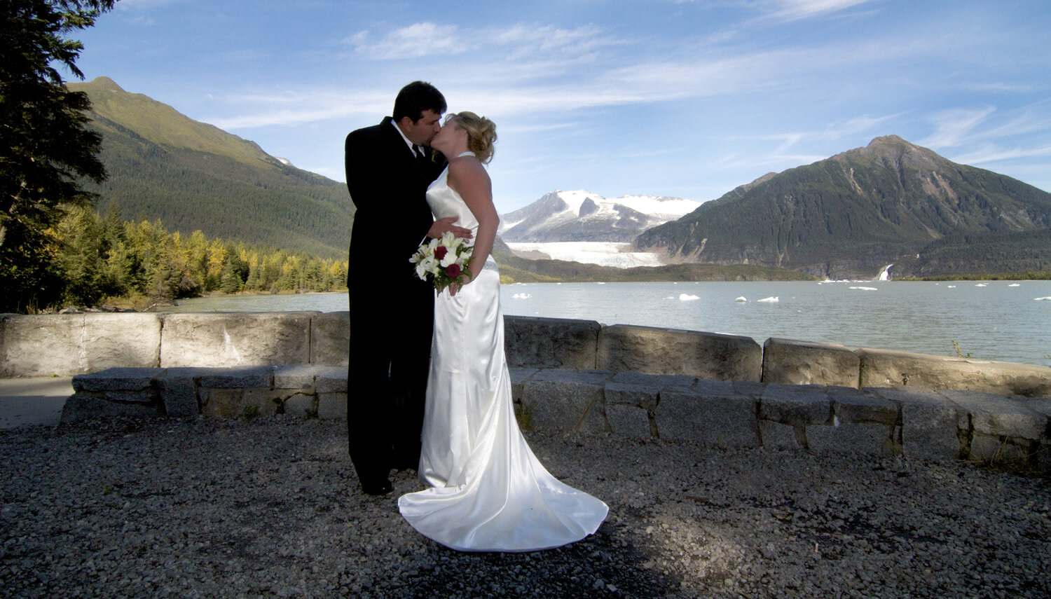 First kiss alongside Mendenhall Lake with a background of lightly clouded blue sky and Mendenhall Glacier