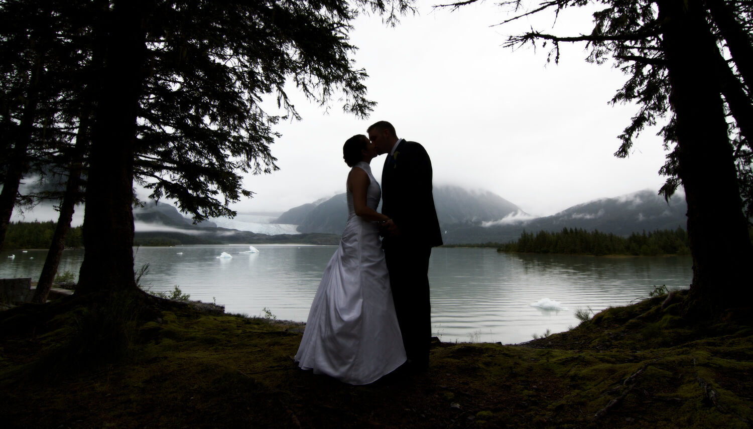 First kiss surrounded by the rain forest with a misty lake and glacier in the background