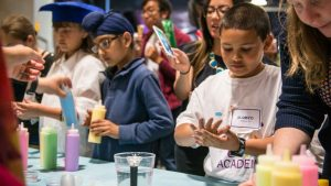 "Students learn how ""disease"" spreads using colored water.  Photo from the Genentech archives."
