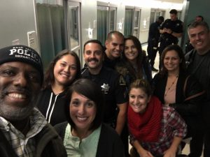 Stanley Roberts, KRON 'People Behaving Badly' personality takes a selfie with SSFPD officers, family and friends of Officer Chon's upon the good news
