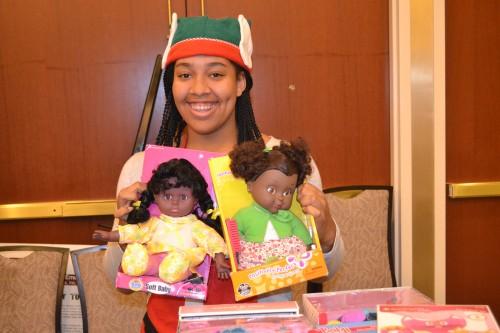 Volunteer elf Makia all smiles, shows two Black dolls.