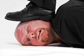 Man lying prone with a shoe stepping on the side of his face