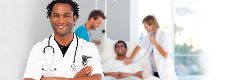 Doctor in hospital room with patient and nurses in the background.