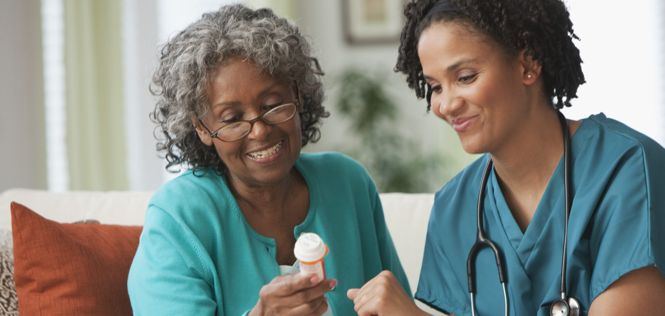 Home Health Aid going over prescription medication with older patient at home.