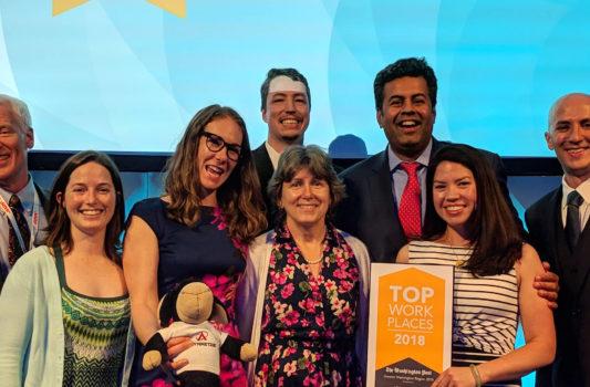 four women four men holding award plaque