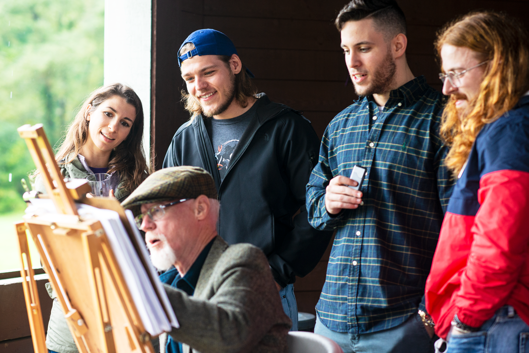 three men and one woman watching artist draw