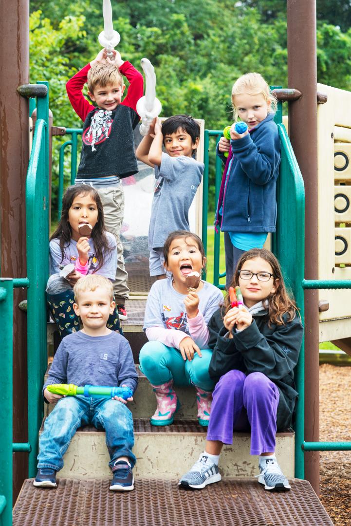 kids at playground eating ice cream smiling