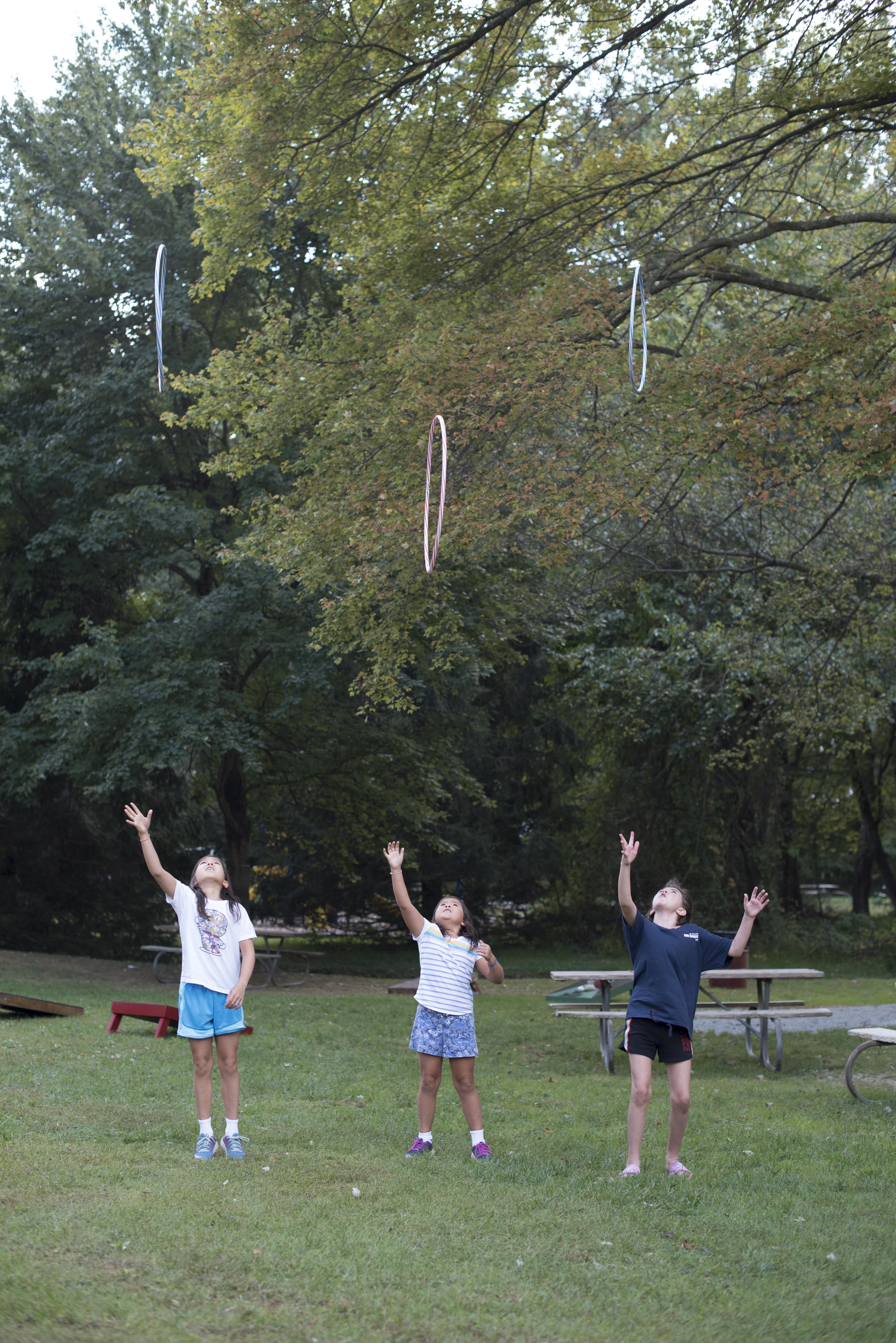 three kids throwing hula hoops into the air Asymmetrik 2019 Family Picnic