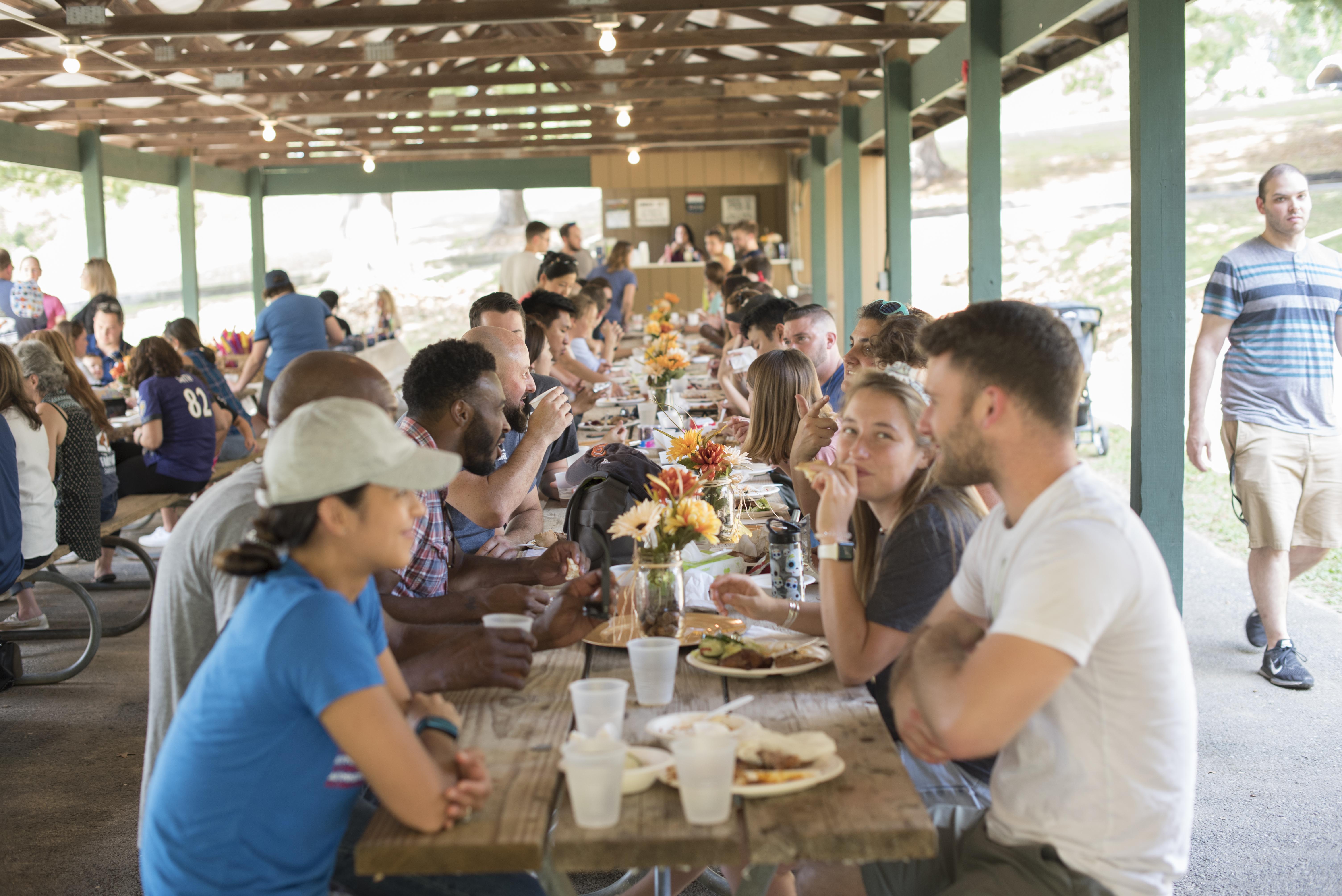 people eating around long picnic table BBQ Asymmetrik 2019 Family Picnic