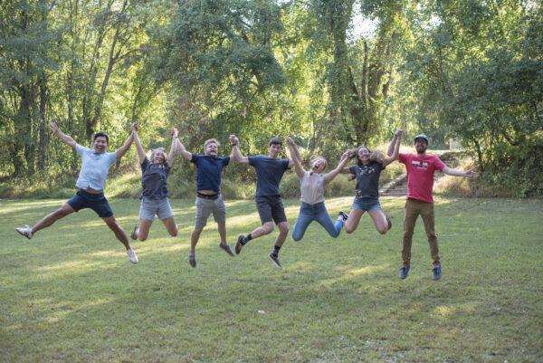 men and women holding hands jumping outside grass Asymmetrik 2019 Family Picnic
