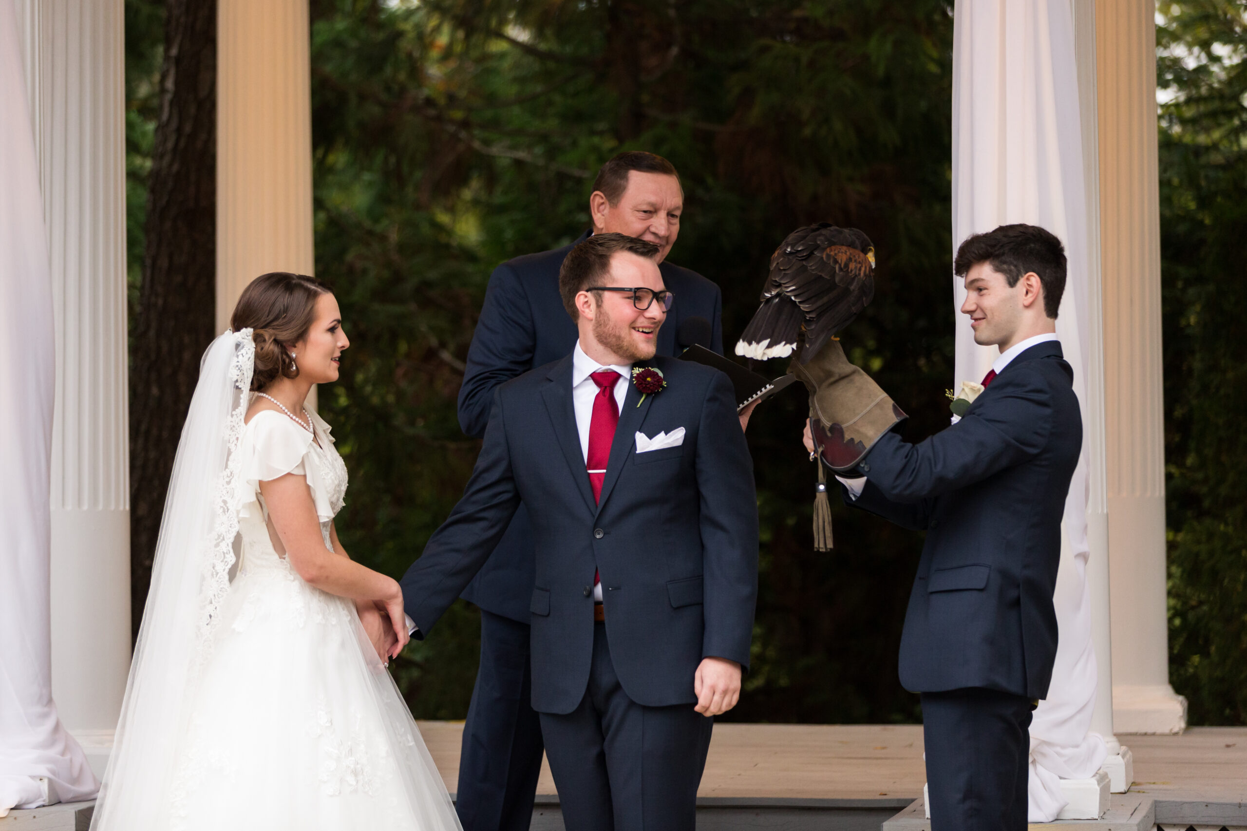 Man and woman at altar with best man holding falcon