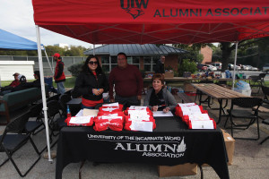 Alumni Board members Laurie Aguillon '11 BBA, Steve Hemphill and Joan Shepack '79 BSN setup the registration table for the Homecoming tailgate and BBQ.