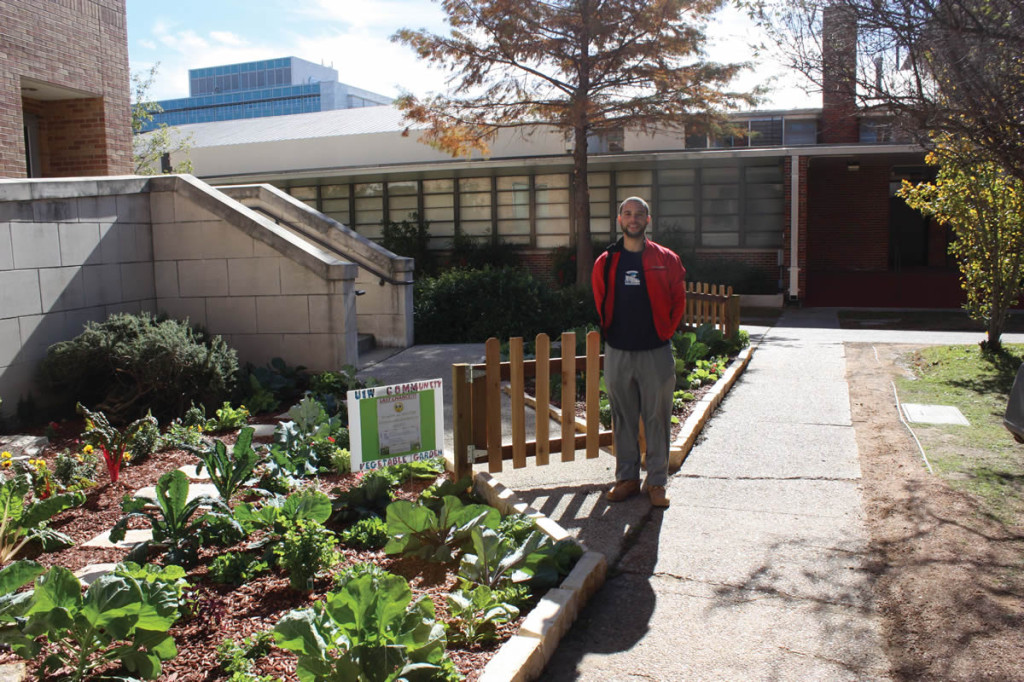 Stephen Lucke poses with the UIW Community Vegetable Garden behind the Gorman Business and Education Center.