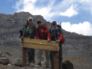 (Pictured L-R) Kim Jordan, a friend who accompanied Magnum; Augustine, a guide from Patagonia; and Mangum at the welcome sign of Base Camp, 14000, where they stayed to acclimate to conditions for three days.