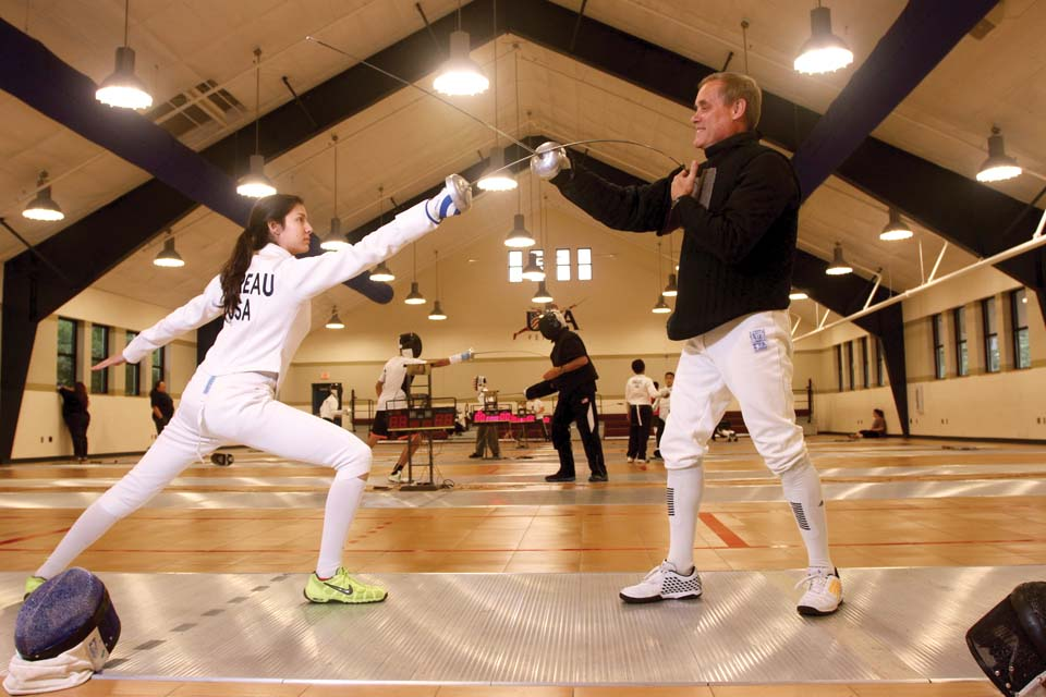 Monet and John Moreau demonstrate a fencing maneuver with epée weapons.