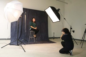 Students work in the lighting studio for photography.