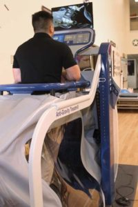 A PT student demonstrates an anti-gravity treadmill used to treat patients in the clinic.